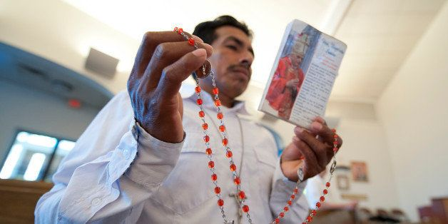 UNITED STATES - August 25: Delfino Velazquez holds his rosary beads as he prays with about 200 people who gathered for an emo
