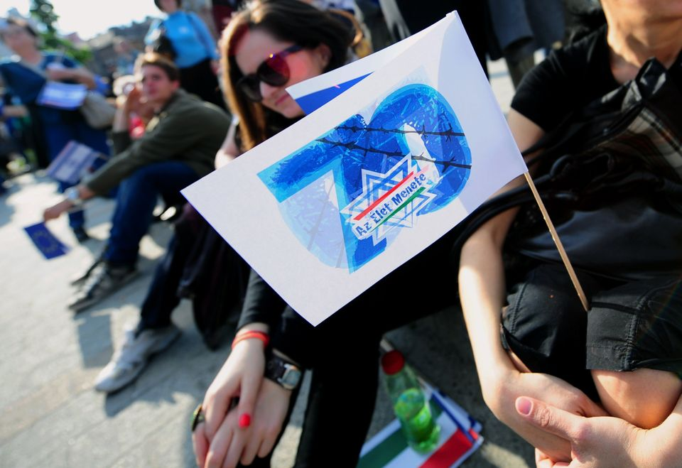 Hungarians and foreigners sit on the pavement with a flag with a text '70 - March of the Living' in Budapest on April 27, 201