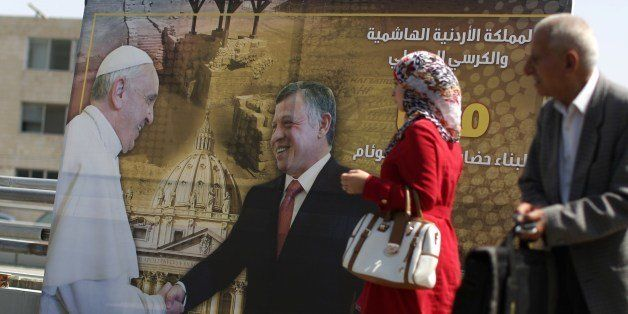 A Jordanian Muslim woman walks past a poster in Amman on May 22, 2014 showing Jordan's King Abdullah II (C) shaking hands wit