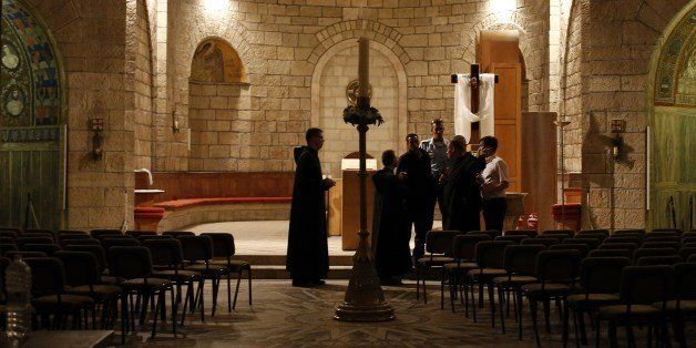 Priests and Israeli policemen inspect a Catholic church on May 26, 2014 after arsonists set fire to it at a contested site in