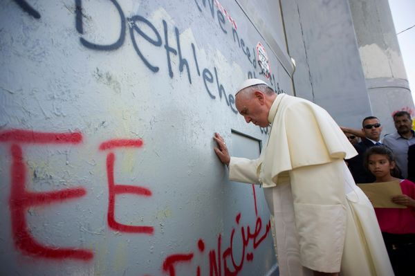 Pope Francis touches the wall that divides Israel from the West Bank, on his way to celebrate a mass in Manger Square next to