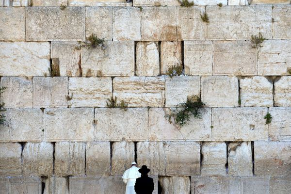 Pope Francis prays at the Western Wall, the holiest place where Jews can pray, as an unidentified Rabbi looks at him, in the