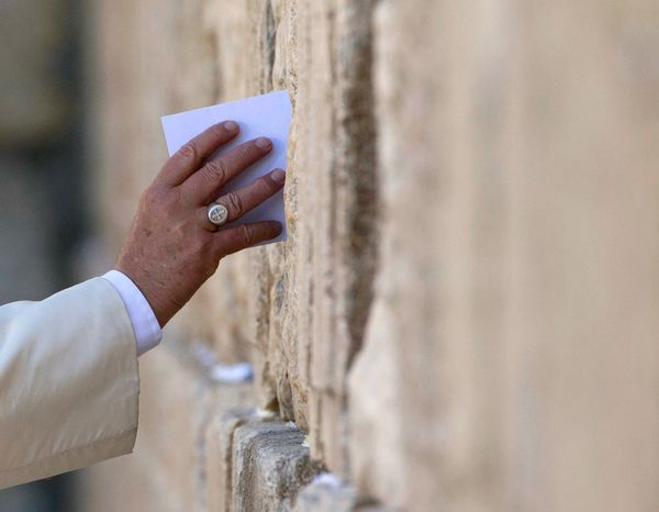 Pope Francis places an envelope in on of the cracks between the stones of the Western Wall, the holiest place where Jews can
