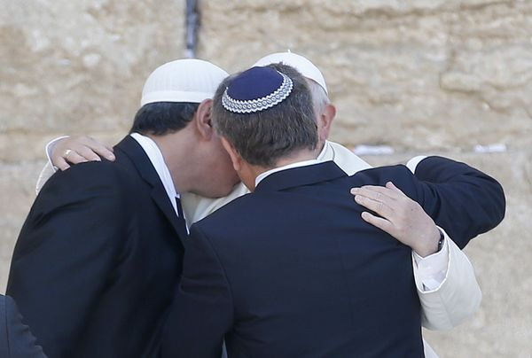 Pope Francis hugs two close Jewish and Muslim friends traveling with him at the Western Wall in Jerusalem's Old City on May 2