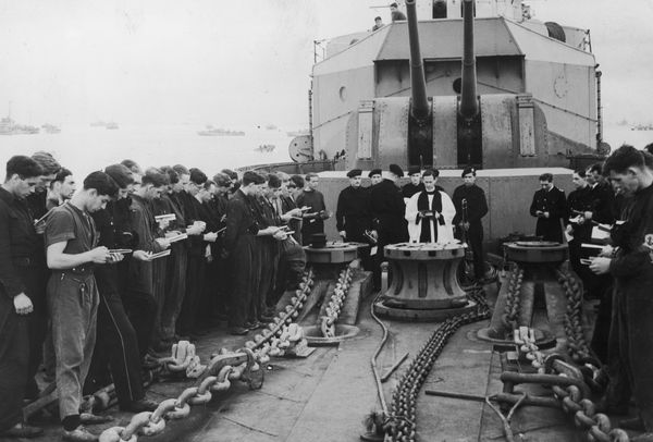 Chaplain saying mass aboard HMS Scylla, laying at anchor off the Normandy coast shortly after the D-Day invasion of France Ju