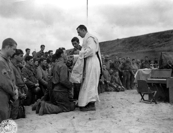 "Father John McGovern gives mass in France during <a href=""https://www.flickr.com/photos/photosnormandie/9576535933/"" target="""