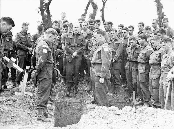 Captain Callum Thompson, a Canadian chaplain, conducting a funeral service in the Normandy bridgehead, France, 16 July 1944.