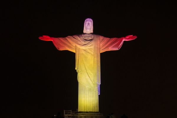 The statue of the Christ the Redeemer is seen lit with the colours of Spain's flag during the changing of all 32 nations' col