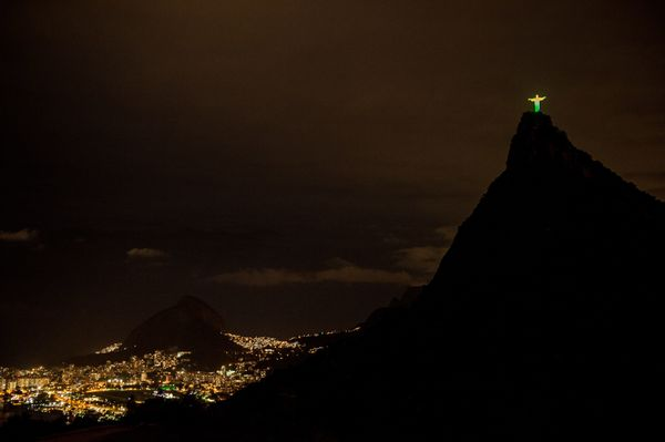 The statue of the Christ the Redeemer is seen lit with the colours of Brazil's flag during the changing of all 32 nations' co