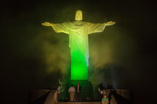 The statue of the Christ the Redeemer is seen lit with the colours of Brazil's flag