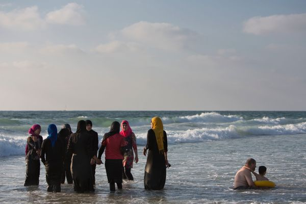 Palestinians enjoy the Mediterranean sea during the Eid al-Fitr holiday, in Tel Aviv, Israel, Saturday, Aug. 10, 2013. The th