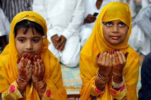 Young Muslim girls offer prayers at Eidgah during Eid al-Fitr in Allahabad, India, Saturday, Aug. 10, 2013. Muslims are celeb