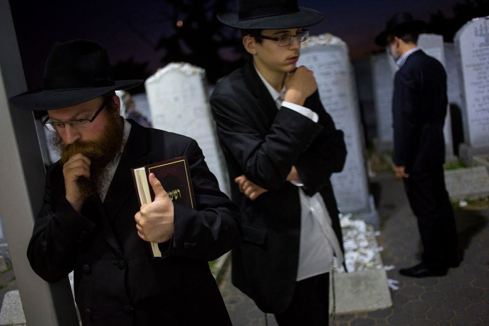 Visitors pray at the gravesite of the Lubavitcher Rebbe, Rabbi Menachem Mendel Schneerson June 30, 2014 at the Old Montefiore