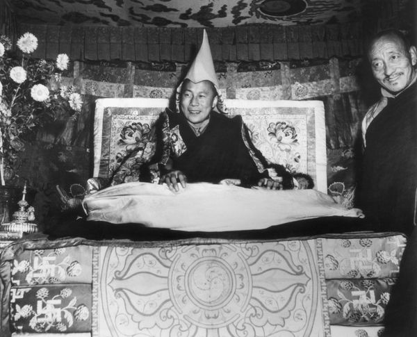 1959: His Holiness the Dalai Lama, Tenzin Gyatso, seated on his throne and wearing the gold peaked cap which is his crown, sm