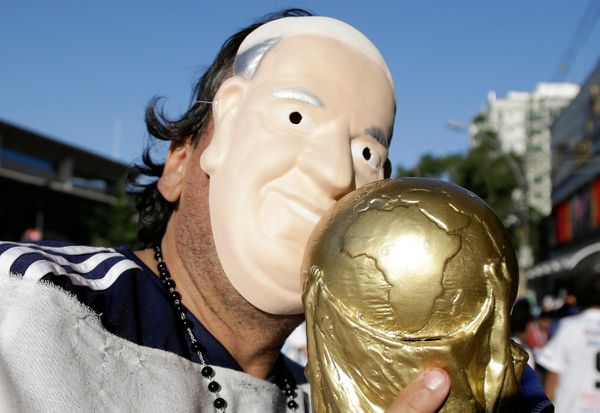 An Argentine fan  wearing a Pope Francis mask Francis kisses a replica of the World Cup trophy before the group F World Cup s