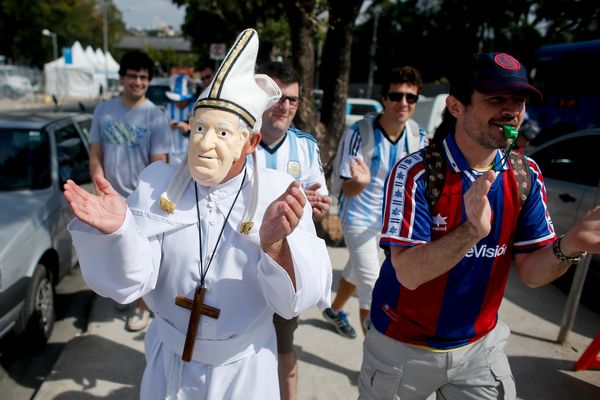 An Argentine fan dressed as Pope Francis cheers for his team outside the Mineirao Stadium in Belo Horizonte, Brazil, Friday,