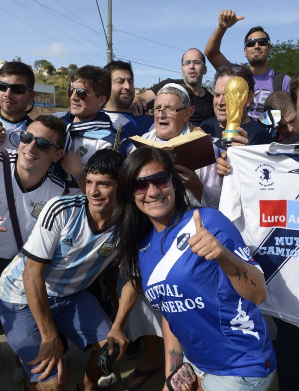 Argentinian fans, one of them posing as Pope Francis, gather at the entrance of 'Cidade do Galo', the base camp of Argentina'