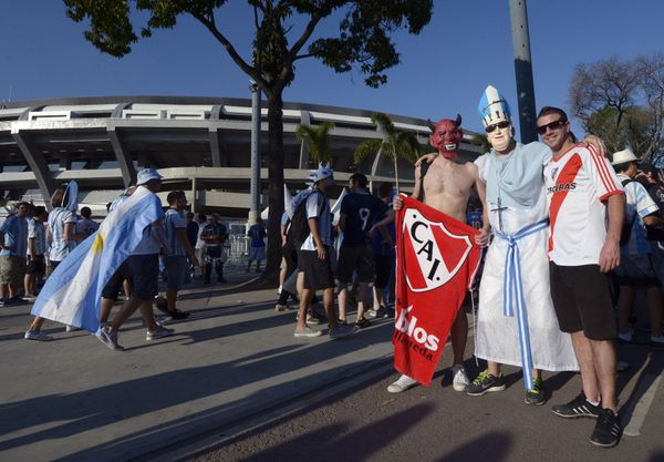 Argentinian supporters pose wearing a mask of a Devil (symbol of Independiente's football club), depicting Pope Francis (2nd