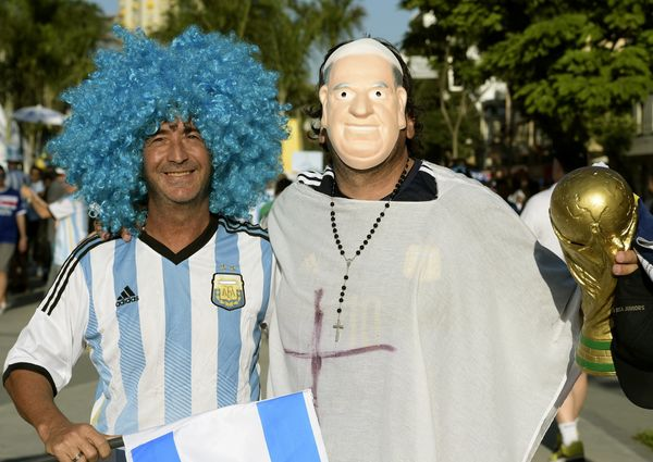 An Argentinian supporter poses wearing a Pope Francis mask and holding a World Cup trophy replica outside of the Maracana Sta