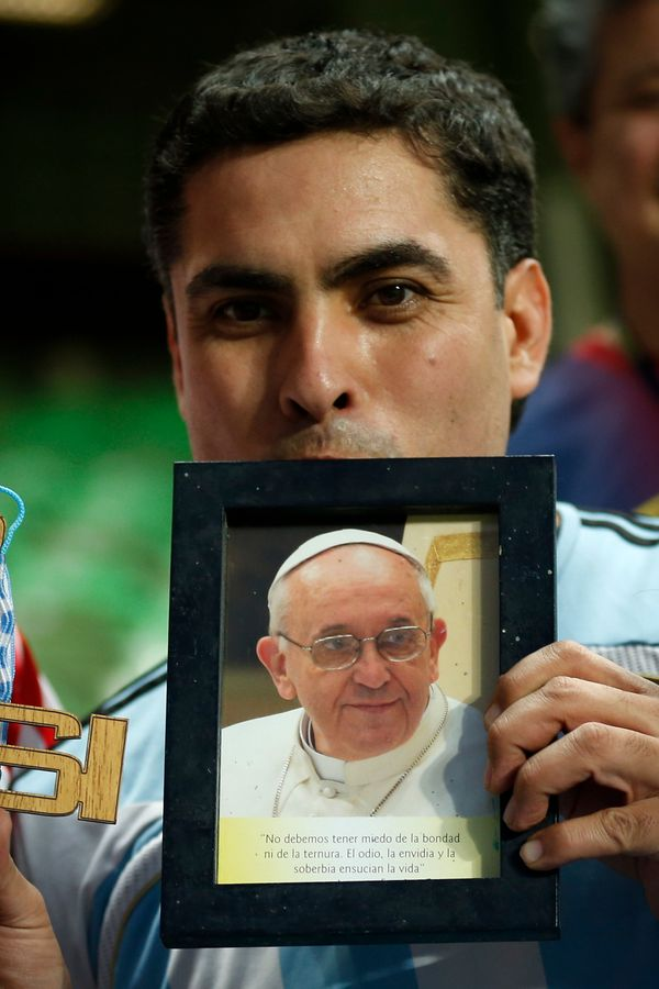 An Argentine fan kisses a photo of Pope Francis before the start of a training session at Independencia Stadium in Belo Horiz