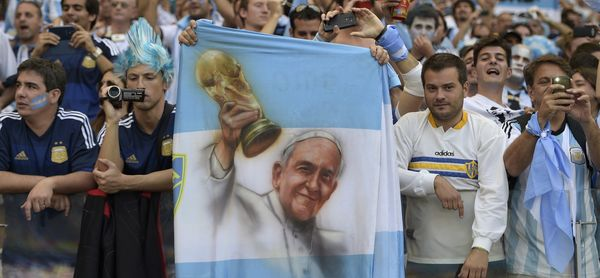 An Argentinian fan holding a portrait of Argentina's Pope Francis cheers with fellow supporters prior to a Group F football m