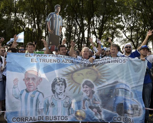 Argentina's supporters hold a banner depecting Pope Francis, Argetina's former football star Diego Maradona and Argentina's f