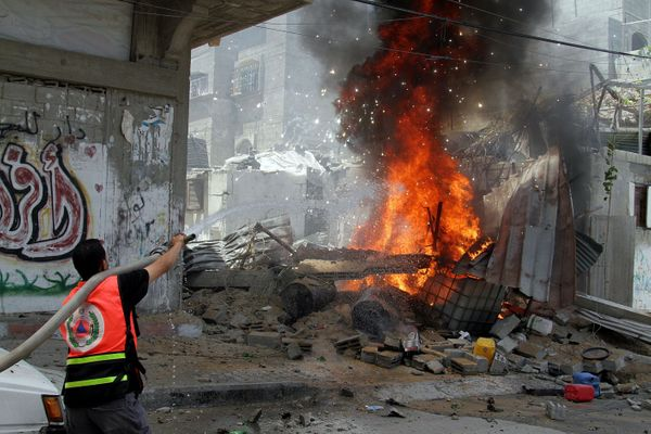 Palestinian firefighters extinguish a fire that broke out after an Israeli air strike hit a car in Gaza City, Gaza on July 14