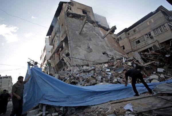 Palestinians cover the ruble of a destroyed house following an overnight Israeli missile strike in Gaza City Monday, July 14,