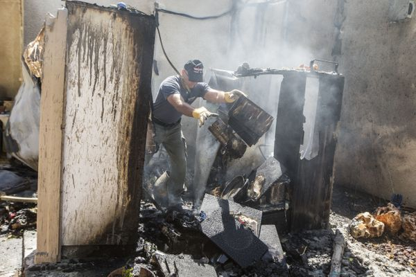 Israeli bomb disposal experts inspect the damage at a house following a rocket attack by Palestinian militants from the Gaza
