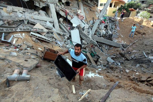 Palestinians inspect a house destroyed in air attacks staged by Israel army within the scope of 'Operation Protective Edge' i