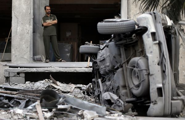 A Palestinian stands looking at damaged cars amid the rubble of destroyed buildings following an Israeli air strike on July 1