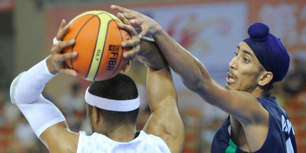 Moon Tae Jong of South Korea (L) passes a ball as Amjyot Singh of India (R) defends during their preliminary round match between South Korea and India at the 26th Asian Basketball Championships in Wuhan in China's central Hubei province on September 17, 2011. South Korea won 84-53. AFP PHOTO / LIU JIN (Photo credit should read LIU JIN/AFP/Getty Images)