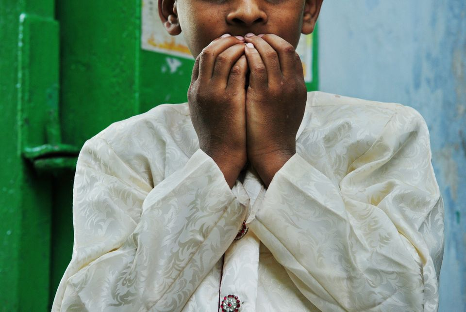 An Indian Muslim child prays as he stands near the entrance to a mosque, as he and other devotees congregated to celebrate th