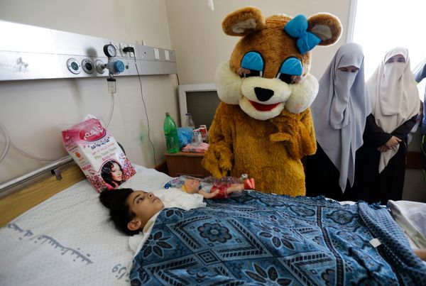 Palestinian Maha al-Sheikh Khalil, 7, left, receives a present by a charity worker dressed as a bear for the Eid al-Fitr holi