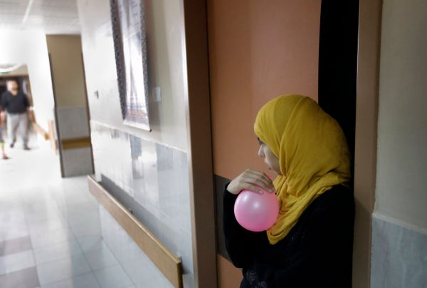 A relative of a child who was wounded in an Israeli strike, blows up a balloon in the corridor of the Shifa hospital in Gaza