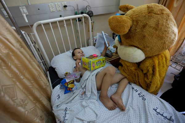 Muhammed al-Ajouz, 4, receives a present by a charity worker dressed as a bear for the Eid al-Fitr holiday, at the Shifa hosp