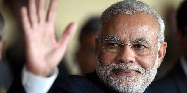 India's Prime Minister Narendra Modi waves while leaving the BRICS-UNASUR Summit at Itamaraty Palace in Brasilia, Brazil on J