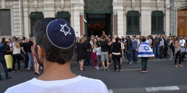 A man wearing a skullcap looks on as people take part in a demonstration called by the Representative Council of Jewish Insti