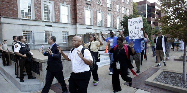 A group of pastors, clergy and protesters march to the office building of St. Louis County Prosecutor Bob McCullough on Augus