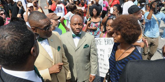 FERGUSON, MO - AUGUST 11:  Members of the Nation of Islam speak to protestors during a protest of the shooting death of 18-ye