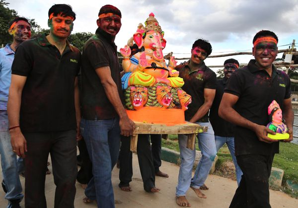Hindu devotees, faces smeared with colored powder, carry a clay idol of elephant-headed Hindu god Ganesha to immerse in a lak