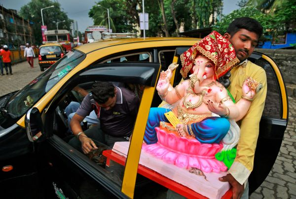 A Hindu devotee carries a clay idol of elephant-headed Hindu god Ganesha into a taxi during Ganesh Chaturthi festival in Mumb