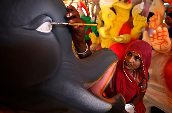 An Indian artisan adds finishing touches to an idol of elephant-headed Hindu god Ganesha at a workshop on the outskirts of Ch