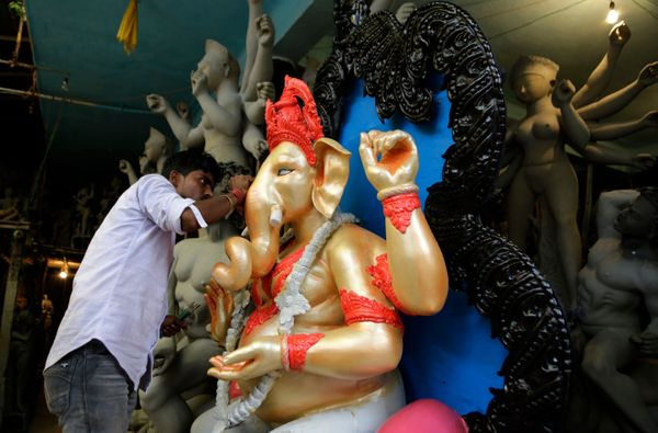 An Indian artist gives finishing touches to an idol of elephant-headed Hindu God Ganesha at a roadside studio in Kolkata, Ind