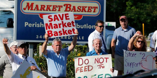 Protesters hold signs and taunt a car entering the site of a Market Basket Supermarket job fair in Andover, Mass., Wednesday,