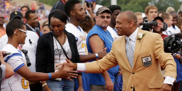 Hall of Fame Inductee Aeneas Williams greets fans as he is introduced during the 2014 Pro Football Hall of Fame Enshrinement