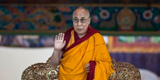 Tibetan spiritual leader the Dalai Lama gestures to devotees before he starts teaching on the fifth day...