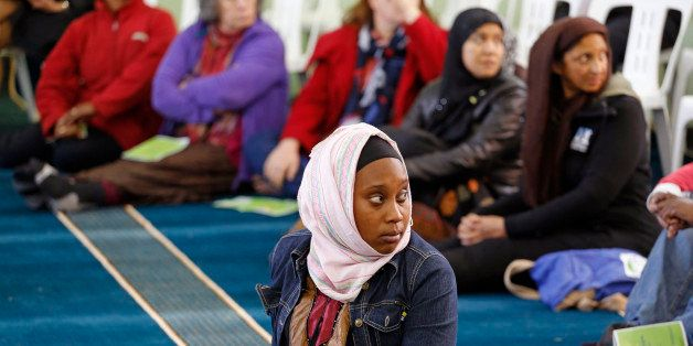 A woman listens inside the Open Mosque, as she and other woman share the same area with men in Cape Town, South Africa, Frida
