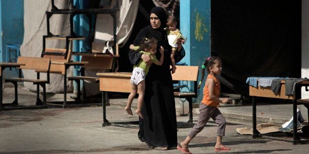 In this Wednesday, Sept. 3, 2014 photo, a Palestinian woman carries two children as she walks in a U.N. school where she live