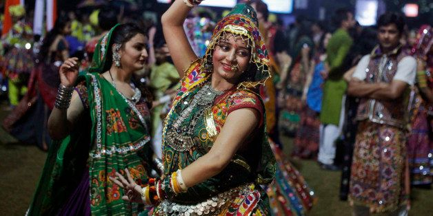 In this Wednesday, Oct. 9, 2013 photo, an Indian woman dressed in traditional finery performs the Garba dance of the Navratri